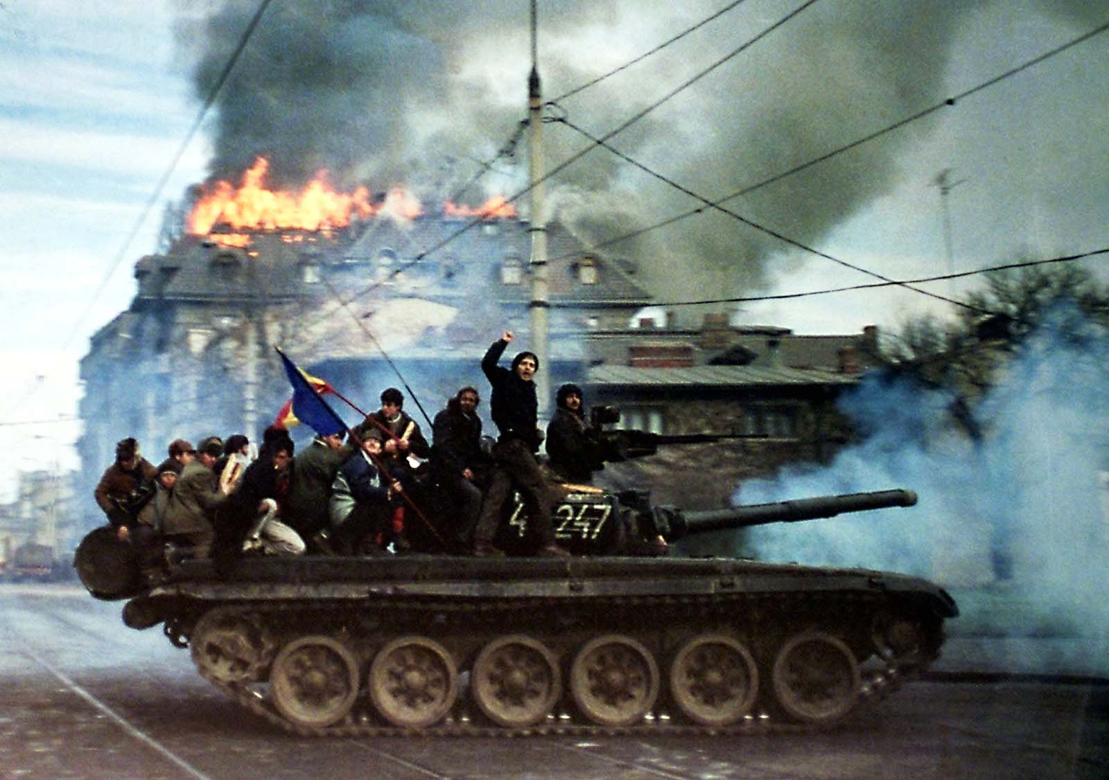 Romanian demonstrators sit on top of a tank as it passes in front of a burning building, December 22 1989.