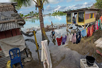 Families in Kiribati, especially those new to the island nation, are often forced to live in marginal areas, where flooding from high tides is increasing.  (Photograph Credit: Kennedy Warne) Click to Enlarge.