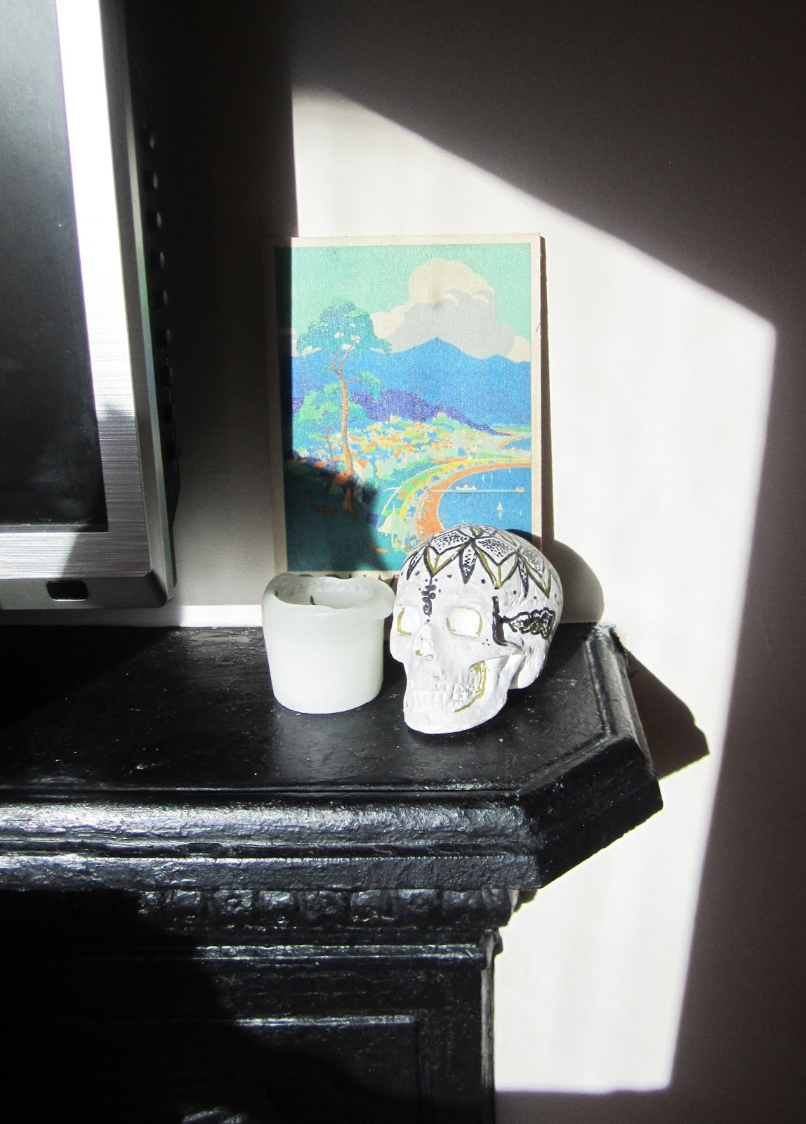 skull painted with mandalas and candle on fireplace