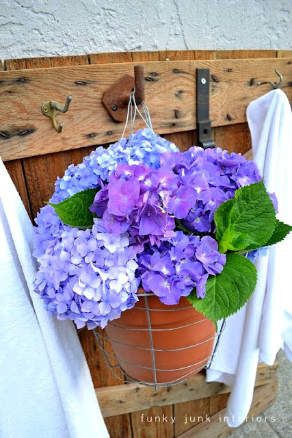 Fresh cut hydrangeas hang from a poolside towel hook area for a punch of summer colour!