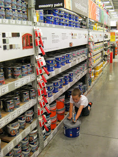 diy store paint aisle kid pushing giant tub of paint