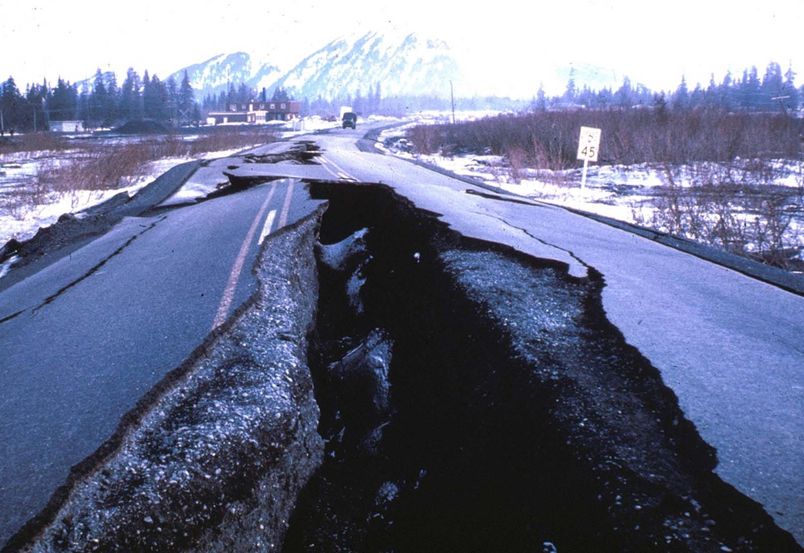 This highway embankment fissured and spread, cracking down the middle. The road was built on thick deposits of alluvium and tidal estuary mud along Turnagain Arm near Portage.