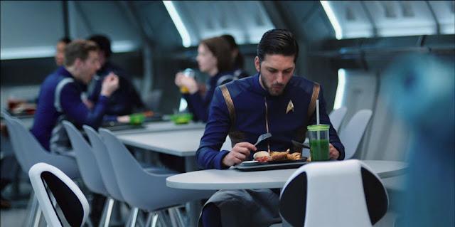 vemos a Sarek e uniforme comiendo solo en una mesa,una hamburguesa con cuchillo y tenedor,  con un batido muy verde con pajita