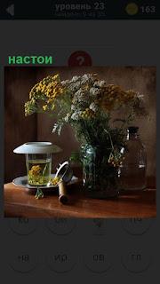 На столе стоит ваза с цветами и рядом настои сделанные из них