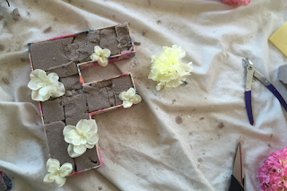 the wooden letter 'f' filled with dry floral foam, and in the process of being filled with artificial flowers