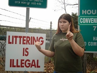 A teenage girl tell others to take note of the littering sign.