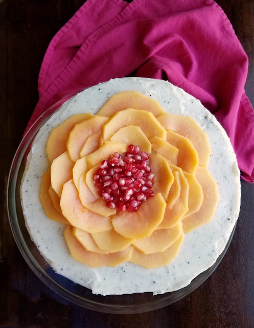 flower made from slices of papaya and pomegranate arils on top of cake