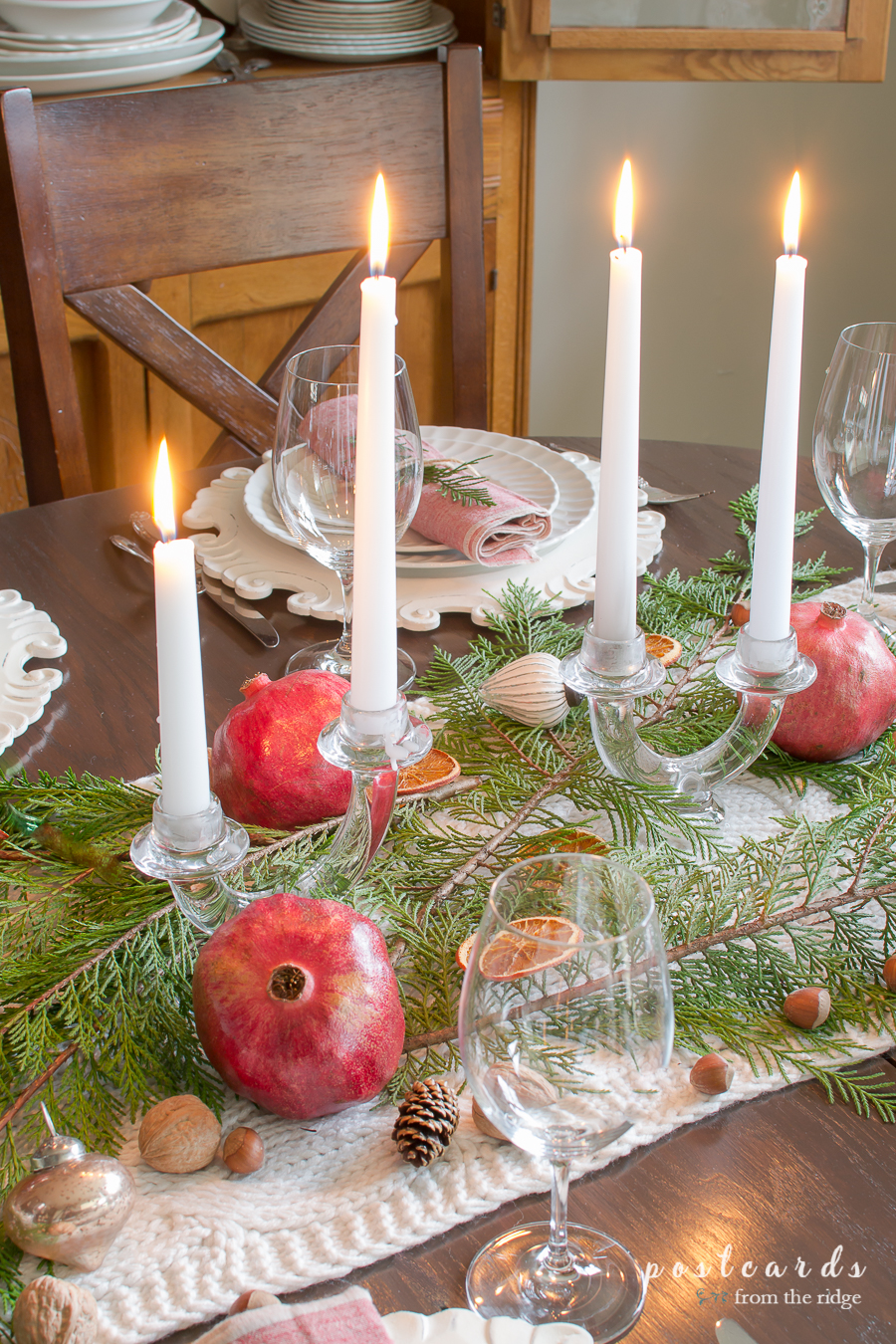 Christmas centerpiece with pomegranates, cypress, nuts and orange slices