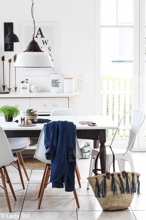 Ibizakorbtasche mit Jeans-Tasseln steht auf dem Küchenboden neben dem weißen Tisch und weißen Stühlen, über der Stuhllehne liegt eine Jeansjacke