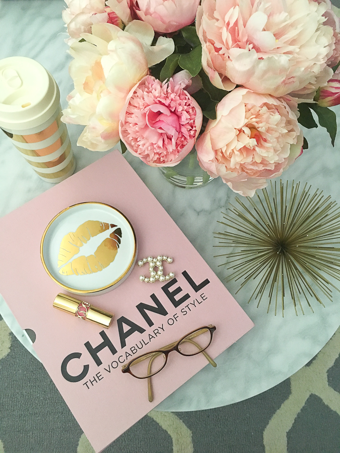 Chanel pearl brooch, Chanel The vocabulary of style book, faux silk peonies in glass vase, Gold urchin, Grey trellis tufted rug, Kate Spade gold striped thermal mug, Oval marble coffee table, Rosanna Gold Trim Porcelain Wine Coaster, YSL lipstick