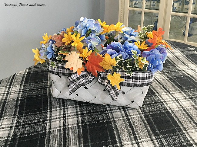 Vintage, Paint and more... using a plaid blanket scarf with an upcycled market basket and faux hydrangeas and fall flowers as a dining room tablescape