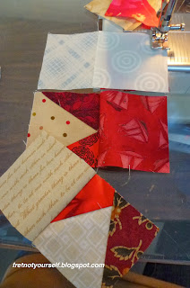 Red and cream squares of a nine-patch are chain pieced into three columns to maintain the order of the pieces.