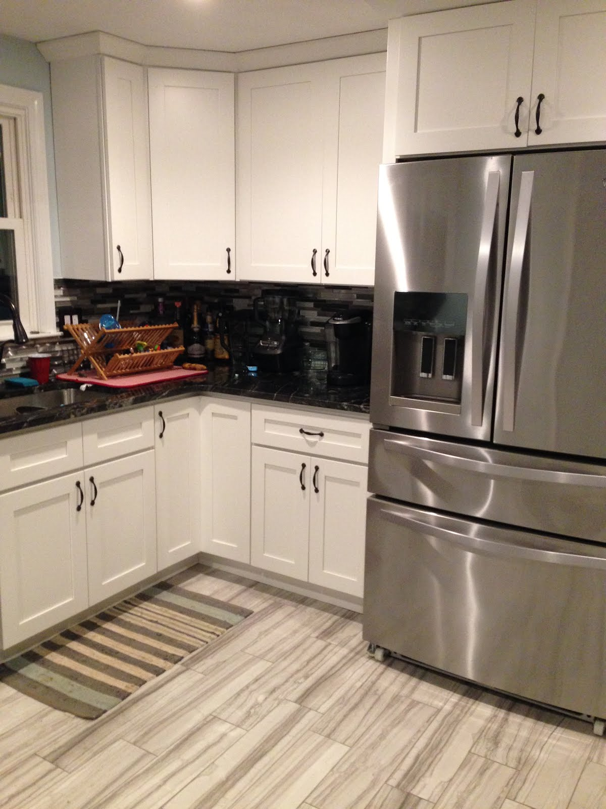 updated kitchen with white cabinets and black countertops