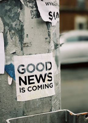 "A sticker reading ""good news is coming"" on an advertising column"