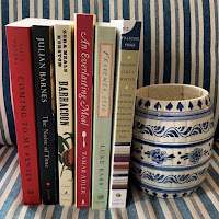 row of books described below on blue and white striped cushion next to blue and white old vase