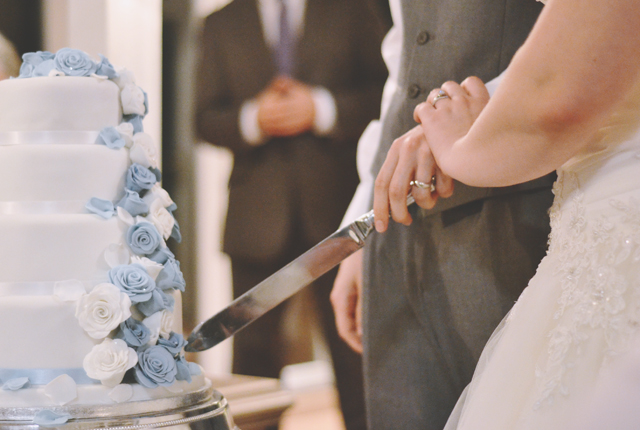 Wedding photo of bride and groom cutting cake