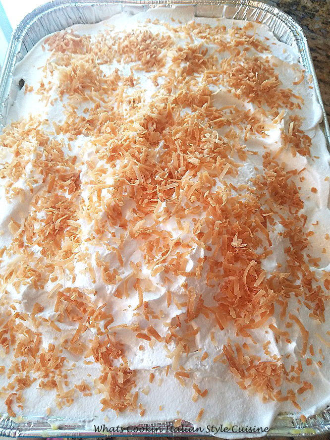 This is a coconut cake with coconut cream pudding that is called poke cakes because you poke holes in the cakes and the coconut cream pudding is throughout the cake then piled high with whipped cream and toasted coconut on top