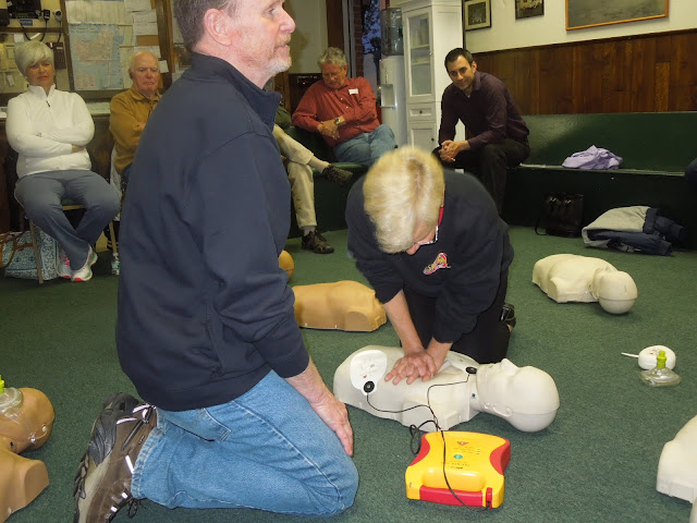 B.Bauer practices CPR while T.Conroy provides instruction in use of AED on patient