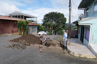 Men digging hole in street of Puriscal.