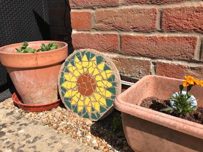 Sunflower mosaic between pots in the garden