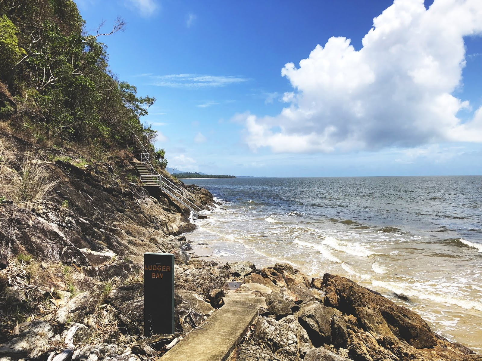 Zejście ze ścieżki Kennedy Walking Track w australijskim miasteczku Mission Beach. Długie białe schody po lewej stornie schodzą w dół na plażę do Morza Koralowego, która już jest zalana przez przypływ. Piaszczysta plaża, duże skarpy i bezchmurne niebo.