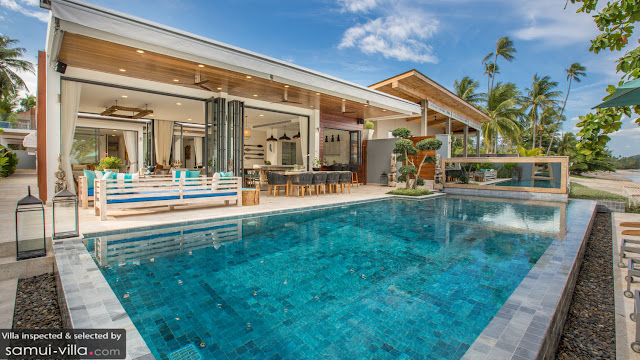 A blue pool with sun loungers in the background and a villa with open bifold doors behind