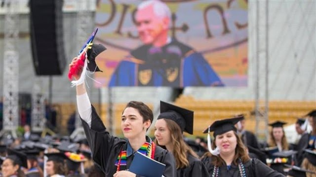 Graduates at Indiana's University of Notre Dame walk out during US Vice President Mike Pence's speech
