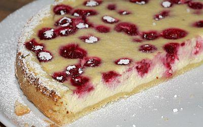 Tarta mágica de ricotta sobre un plato. Una porción de la tarta ha sido cortada.