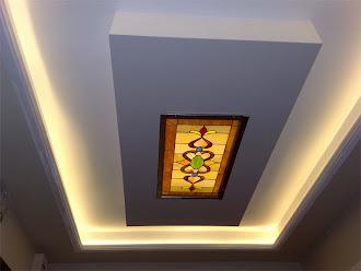 Işıklı dikdörtgenin merkezinde ışıklı bir tablo olan kartonpiyer asma tavan
