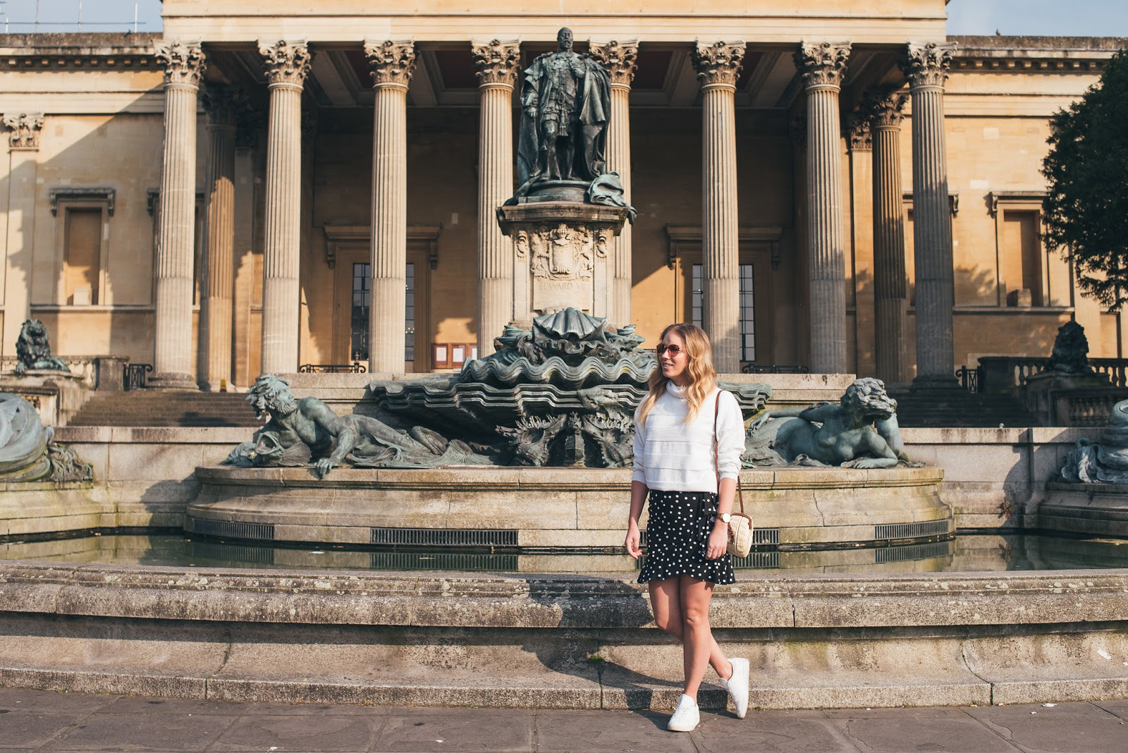 Rachel Emily standing outside of Victoria Rooms Pillars in spring summer transitional outfit