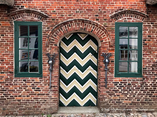 White and green wooden door and windows of a red brick cottage.