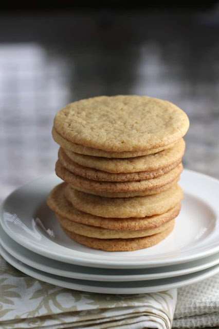 Maple cookies stacked on a plate.