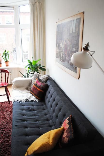 Een stoffen Chesterfield bank in een kamer in bohemien sfeer met veel planten en vintage spullen.