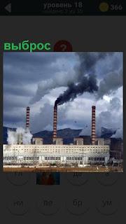 Здание завода, из труб идет выброс в небо вредных веществ