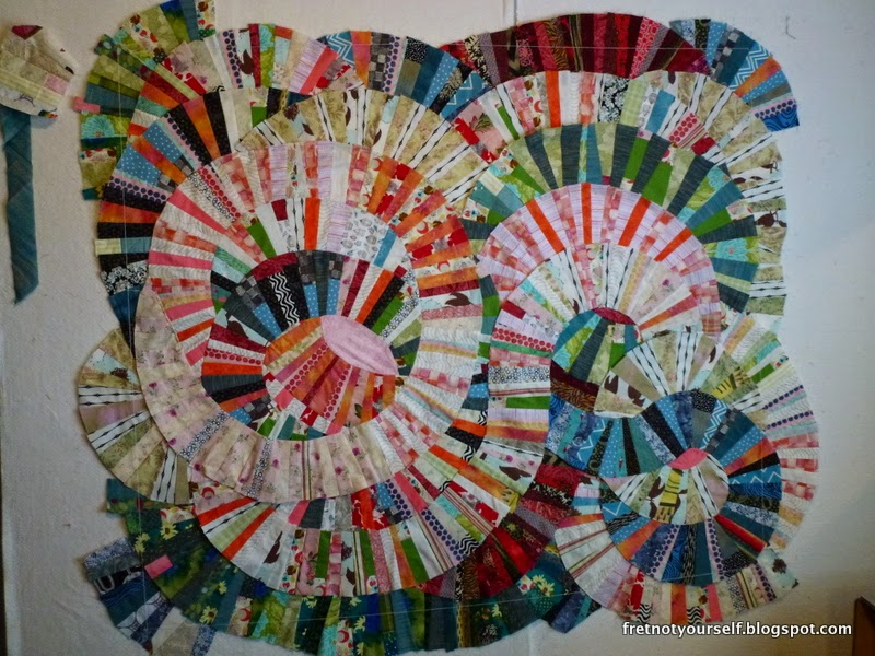 Improvisational curve quilt in shades of pink, coral, red, blue, green and white