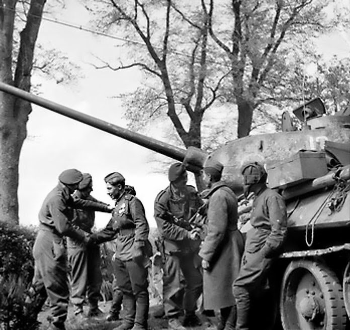 Men of the British 6th Airborne Division greet the crew of a T-34/85 tank near Wismar