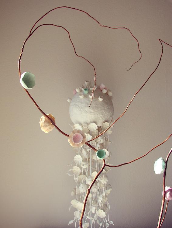 Rami con fiori di carta e alzata con ghirlande , allestimento in cartapesta