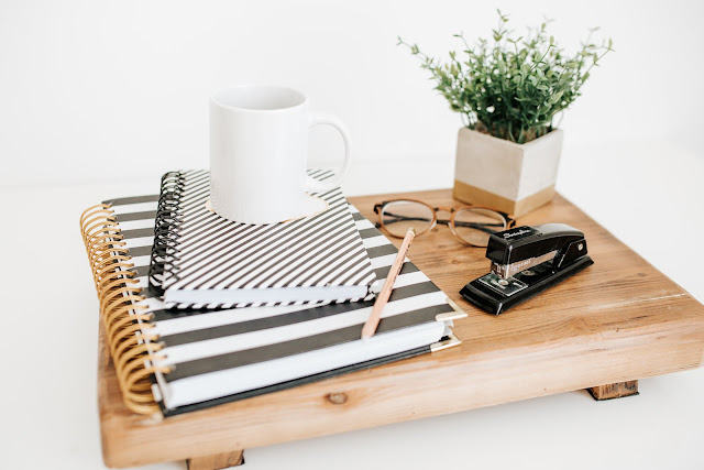 table with two notebooks and a stapler and a coffee mug and a pair of glasses