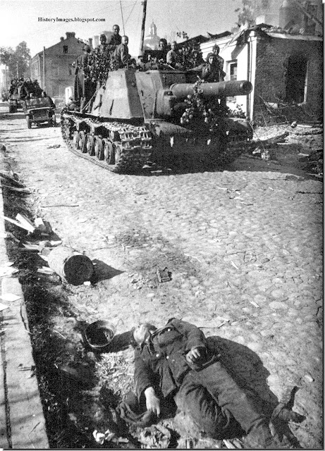 Soviet ISU-152 self-propelled gun move past dead German soldiers in Polotsk