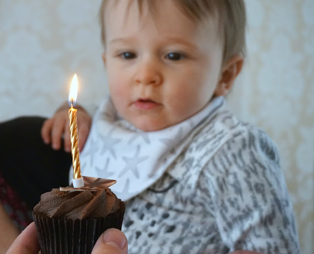 baby boy looking at a candle on a chocolate cupcake