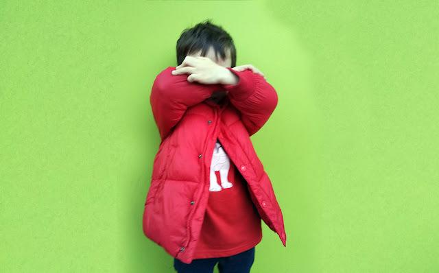 fondo verde, mi hijo 5 años con chaqueta roja jersey rojo se tapa la cara