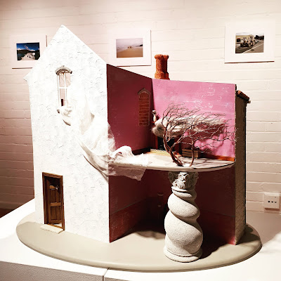 One-twelfth scale model of a two-story building on display in a gallery.