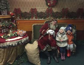 children meeting Santa at Whitehouse farm sitting in his grotto
