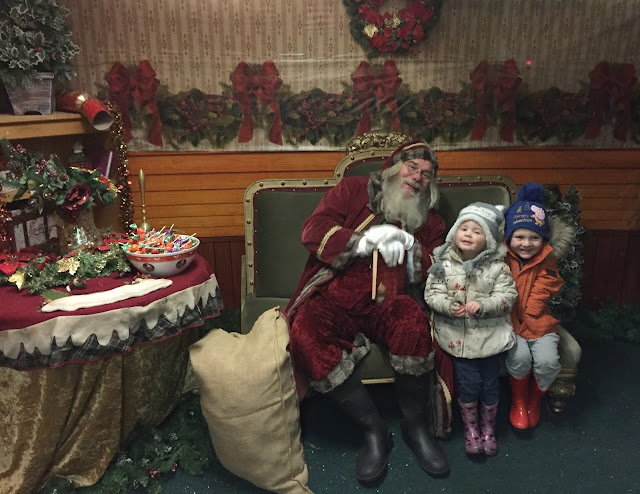 children meeting Santa at Whitehouse farm sitting in his grotto