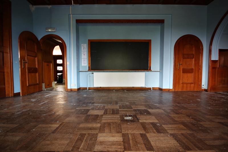 vue de la pièce principale couverte de parquet marqué par la poussière, et mur sur lequel un vieu tableau noir est accroché