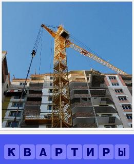 стоит кран и строится дом, в котором будущие квартиры
