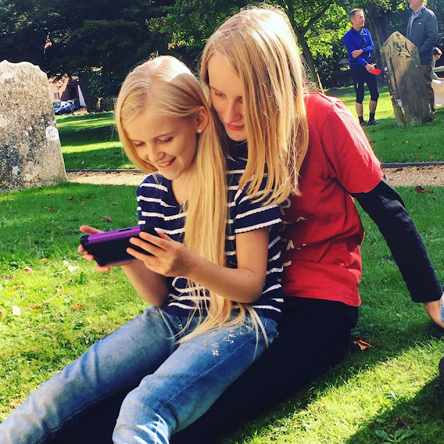 sisters playing on phone