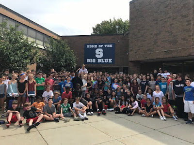 This image shows our current 8th Grade class at Swampscott Middle School gathered outside in front of the building. The students are celebrating the new home of the Big Blue sign.