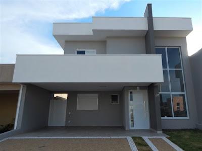 Composta em tons de cinza para as paredes e branco para esquadrias e platibandas, a fachada desta casa é ordenada pelo painel ortogonal mais escuro em destaque, que separa a grande janela com pé-direito duplo dos demais elementos construtivos.