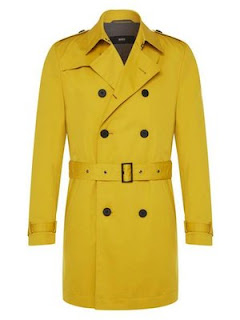 A bright mustard yellow trenchcoat done up with a thick yellow belt across the middle of it with big bold black buttons on a white background.